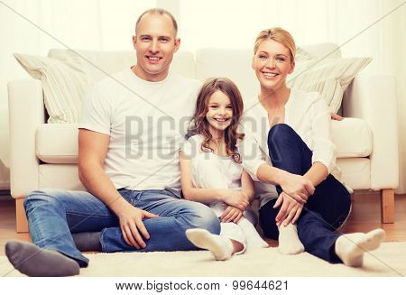 family, child and home concept - smiling parents and little girl sitting on floor at home