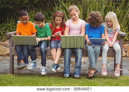 Kids sitting on a park bench with laptops
