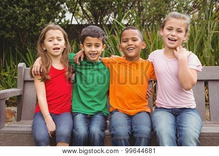 Happy children sitting together on a bench and looking at the camera