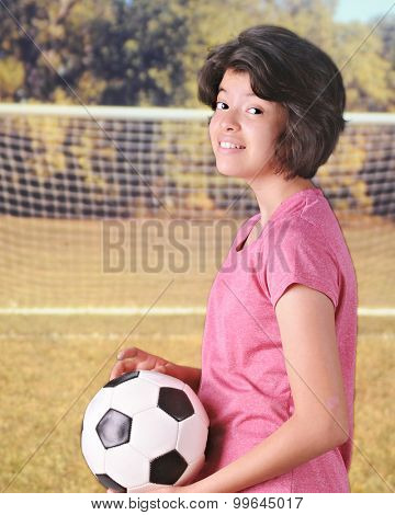 Close-up of a young teen girl carrying her soccer ball near the goal.