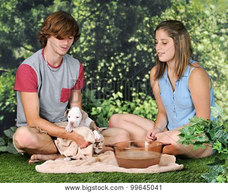 A teen boy drying his new puppy out on a lawn as he girlfriend looks on.