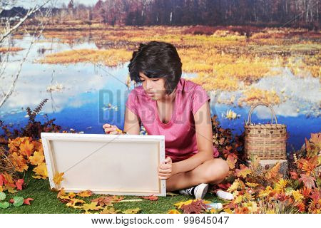 A young Hispanic teen girl sitting on the grass by the edge of a pond.  She's holding a canvas as she begins to paint the fall scenery around her.