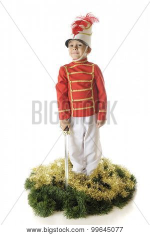 A handsome preschool Christmas soldier standing straight and tall with his sword down by his side.  He's surrounded by green and gold garland.  On a white background.