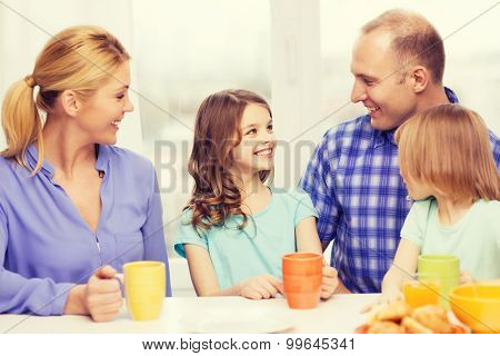 food, family, children, hapiness and people concept - happy family with two kids having breakfast at home