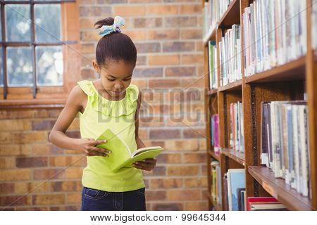 Student reading a book in a library at the elementary school