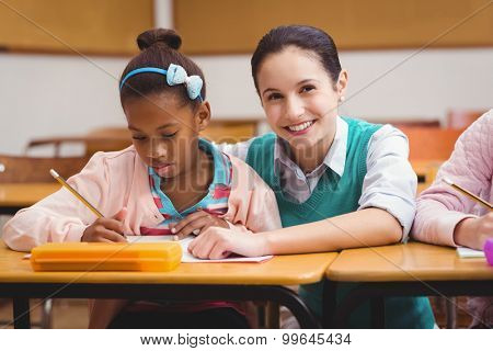 Teacher helping girl during class at the elementary school