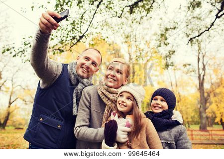 family, childhood, season, technology and people concept - happy family taking selfie with smartphone in autumn park