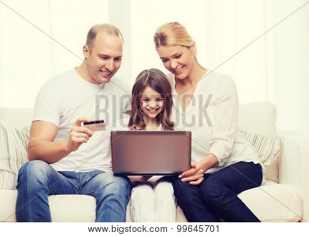 family, child, technology, money and home concept - smiling parents and little girl with laptop and credit card at home