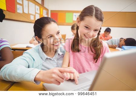Teacher using laptop with pupil at the elementary school