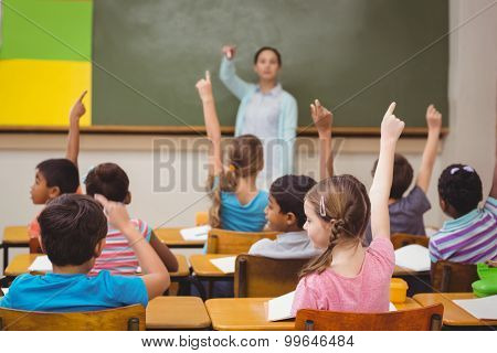 Teacher asking a question to her class at the elementary school