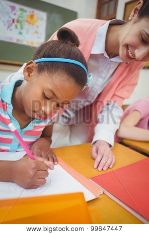 Pupil and teacher at desk in classroom at the elementary school