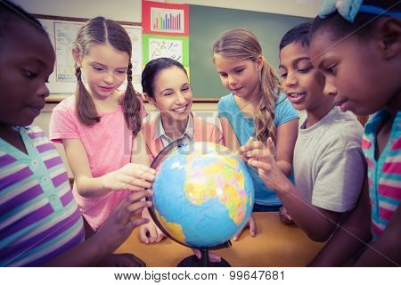 Teacher and pupils looking at globe at the elementary school
