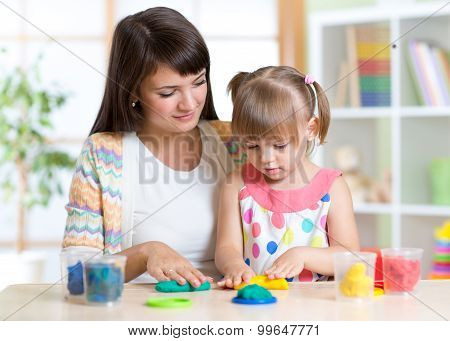 Young woman and kid playing with colorful clay molding different shapes