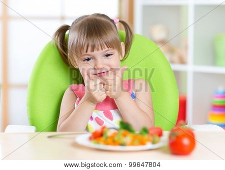 Little girl with vegetables food showing thumb up