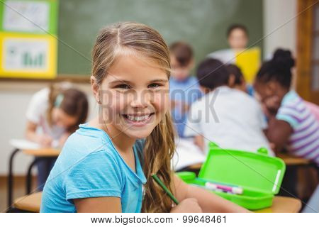 Pupil smiling at camera in classroom at the elementary school