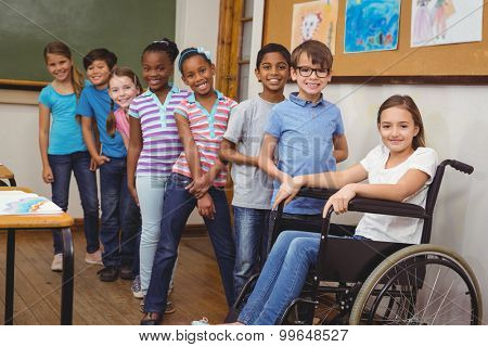 Disabled pupil smiling at camera with classmates at the elementary school