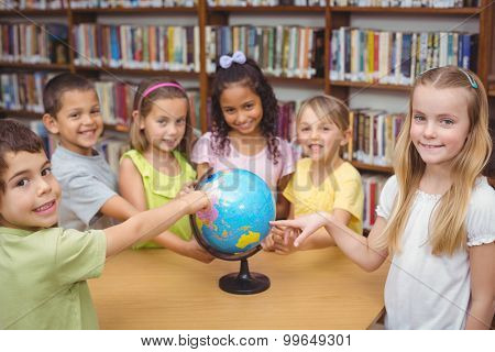 Pupils smiling at camera in library pointing to globe at the elementary school