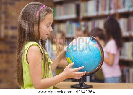 Pupil in library looking at globe at the elementary school