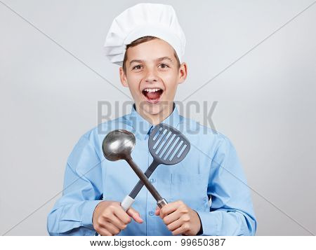 Young Cheerful Teenager With Ladle And Humor In A Chef's Hat. On White Background, Studio