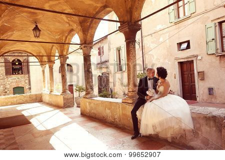 Bride And Groom Sitting Near Old Building