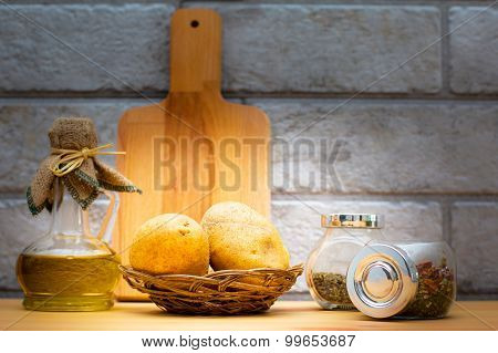 Jug Of Olive Oil, Potatoes, Cutting Board And Spices In The Jars