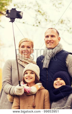 family, childhood, season, technology and people concept - happy family taking selfie with smartphone and monopod in autumn park