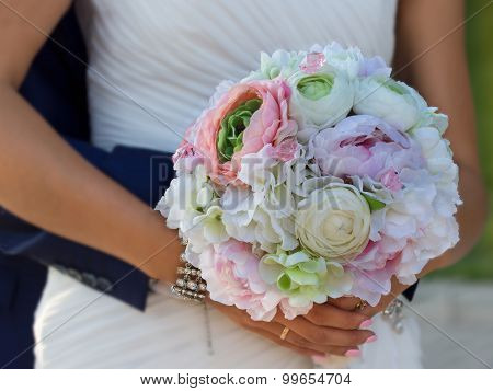 flower bouqet in hands of bride which groom embracing