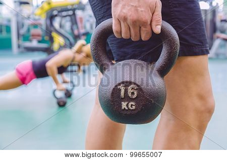 Man holding kettlebell and woman doing pushups in kettlebells
