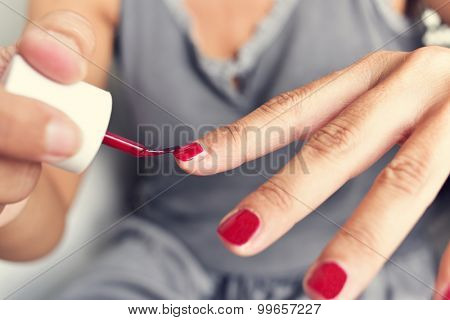 closeup of a young woman applying red nail polish to her fingernails