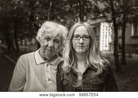 Outdoors portrait of a grandmother and her granddaughter teenager. Black and white photo