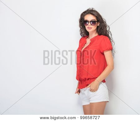 Side view picture of a sexy young woman looking at the camera while holding her hands in pockets.
