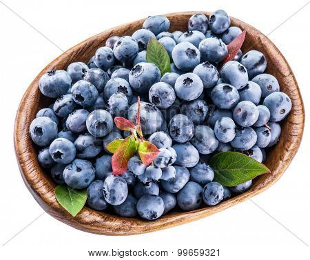 Ripe blueberries in the wooden bowl isolated on a white background.