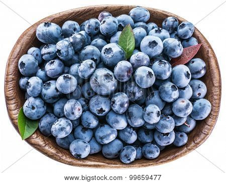 Ripe blueberries in the wooden bowl. Top view. File contains clipping paths.