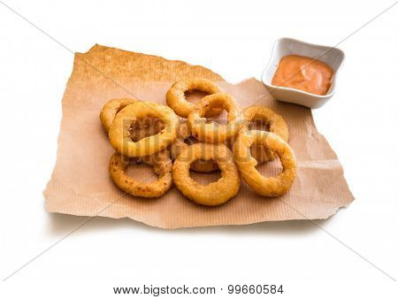 onion rings on parchment with sauce isolated on a white background