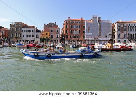 VENICE, ITALY - SEPTEMBER 2014: A man sitting in the SDA Express courier barge navigating the Grand canal in Venice,Italy on September 15, 2014. Barge is the  transportation to carry freight in Venice