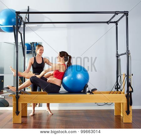pregnant woman pilates reformer cadillac fitball exercise workout with personal trainer