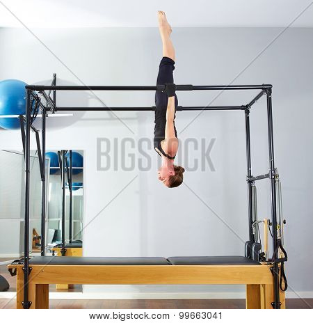 Pilates woman in cadillac acrobatic upside down balance reformer exercise at gym