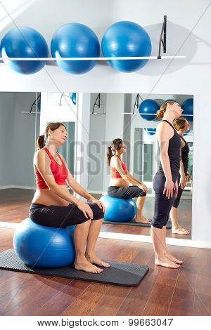 pregnant woman pilates exercise fitball at gym with personal trainer