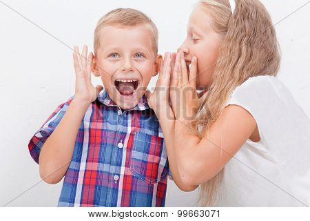 Teenage girl whispering in the ear of a secret teen boys on white  background