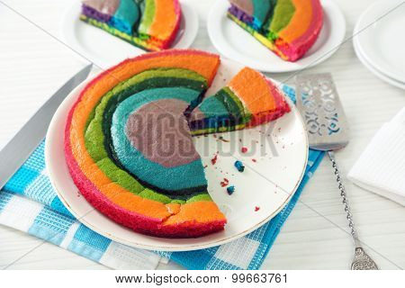 Delicious rainbow cake on plate, on  light background