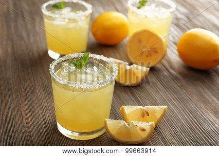 Glasses of lemon juice on wooden table, closeup