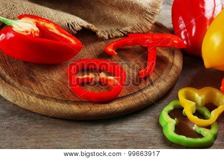 Pieced of color peppers on wooden cutting board, closeup
