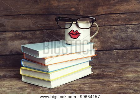 Vintage books and cup with lips on wooden background