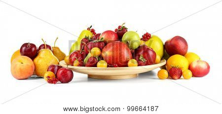 Heap of fresh fruits and berries on plate isolated on white