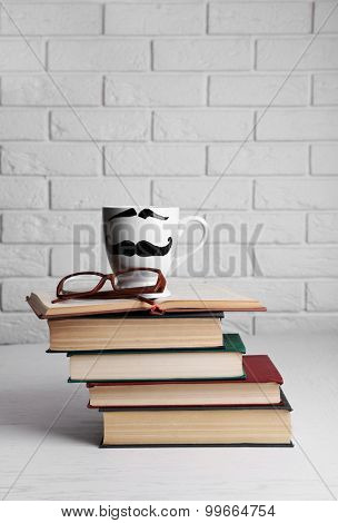 Vintage books and cup with mustache on wooden table on brick wall background