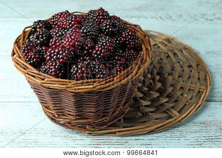 Heap of sweet blackberries in basket on table close up