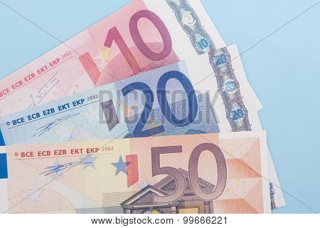 Eighty euro in various notes on light blue background