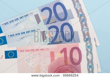 Fifty euro in various notes on light blue background