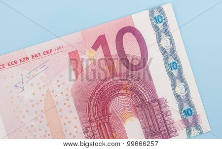 Single ten euro note on light blue background