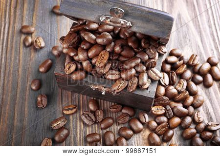 Coffee beans in chest on wooden table close up